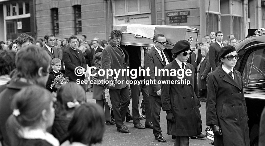 The funeral of Mrs Maura Meehan, 31 years, of Brantry Street, Belfast, exits unto the Falls Road from Clonard Street.  Maura Meehan who, along with her sister Dorothy Maguire, were members of Cumann na mBan, the Women's IRA, were the first members of that organisation to die in the Troubles.  They died in a disputed shooting incident involving a British Army patrol in the Lower Falls. They were allegedly sounding the car horn of a vehicle driven by William Patrick Davidson to warn of the presence of soldiers. The soldiers claimed that a gun was pointed at them.  19711023042MM4..Copyright Image from Victor Patterson, 54 Dorchester Park, Belfast, UK, BT9 6RJ..Tel: +44 28 9066 1296.Mob: +44 7802 353836.Voicemail +44 20 8816 7153.Skype: victorpattersonbelfast.Email: victorpatterson@me.com.Email: victorpatterson@ireland.com (back-up)..IMPORTANT: If you wish to use this image or any other of my images please go to www.victorpatterson.com and click on the Terms & Conditions. Then contact me by email or phone with the reference number(s) of the image(s) concerned.