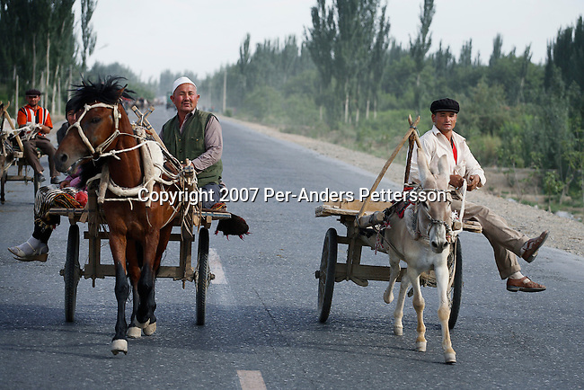 AKSU, CHINA - JUNE 19: Villagers travel home by horse cart from a weekly market on June 19, 2007 outside Aksu, China. Villagers come to Aksu to trade their vegetables and goods. (Photo by Per-Anders Pettersson)....
