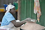 A woman sifts sorghum flour as she prepares food for the Loreto Primary School in Rumbek, South Sudan. The school is run by the Institute for the Blessed Virgin Mary--the Loreto Sisters--of Ireland. Children who come to the school eat twice a day, often the only food they get.