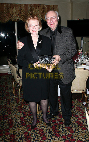 NANNY & PHILIP BOSCO.8th Annual Garden State Awards Gala celebrating closing night of the 2010 New Jersey Film Festival held at the English Manor, Ocean Township, New Jersey, USA, 28th March 2010..full length glasses phillip back tie grey gray suit jacket married husband wife wrap dress holding glass bowl .CAP/ADM/PZ.©Paul Zimmerman/Admedia/Capital Pictures