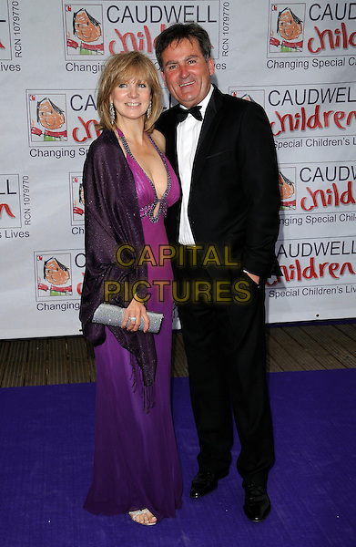 GUEST & RICHARD KEYS.The Caudwell Children's Butterfly Ball, Battersea Evolution, Battersea Park, London, England..May 14th, 2009.full length black tuxedo wrap purple dress silver clutch bag .CAP/CAN.©Can Nguyen/Capital Pictures.
