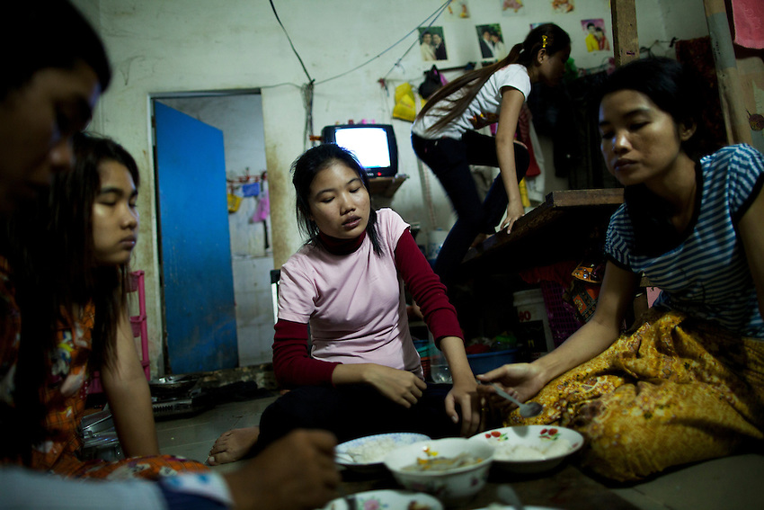 """Sorn Tola (pink shirt), a 22-year-old garment worker from Prey Veng province, eats dinner in the evening with her two sisters and fiancé, in Phnom Penh, Cambodia, Sept 8, 2011. Sorn Tola has been working at the Shen Zhou factory for two years. Every six months she receives a new short-term contract, but there is no increase in the fixed salary (US$61 per month). She worked at another factory for two years before getting a job at Shen Zhou. Sorn Tola works from 7 a.m. until 4 p.m., with a 1-hour lunch break. On most days she also works a 2-hour overtime shift (for which she receives pay of time and a half), and finishes work at 6 p.m. """"I sometimes feel really tired after work because I have to work harder to get more salary,"""" she said, explaining that there are incentives based on output. Her fixed salary is US$61 dollars per month, but last month she says she earned $270 because her sewing output was high. """"I can earn more if I sew a lot of clothes. This system makes workers work harder to get more salary,"""" she said. Sorn Tola said that she doesn't know where the clothes that she makes will be sent or sold. She lives with two of her sisters, her fiancé, and two other friends who are all working for nearby factories. The rent for the 20-meter square room is US$40 per month. Before the minimum wage was increased from US$56 to $61 in October 2010, the rent was only US$25. Most of the housing blocks that garment workers live in are owned by the factories, so to counter the wage increase, most factories simply raised the workers' rent. Every month, Sorn Tola spends about $50 on her living expenses. """"I don't send money to anyone. I try to save all the leftover money every month, but I have no plan for that money yet,"""" she said. Every day Sorn Tola spends about 75 cents (US) to US$1 on food, usually fish, meat and vegetables. """"The amount we spend depends on the types of food we eat. Some days if we have more delicious food, we spend more,"""" she said."""
