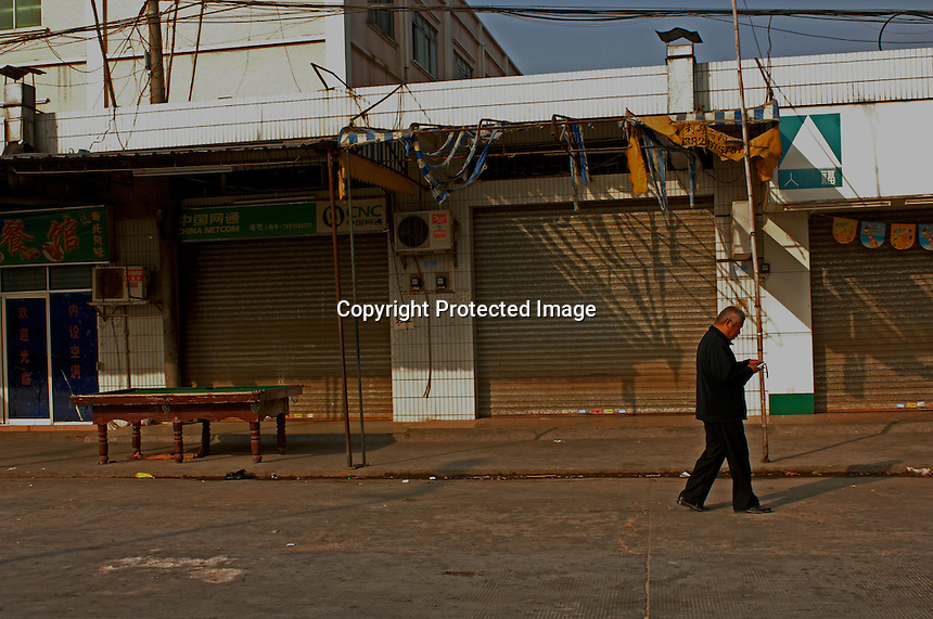 An old man passes a stree of closed shops, Dingfu Factory in Houjie Town, Donguan, China.  As the economy changes and Chinese labour gets more expensive, factories are cosing leaving ghost towns behind them.<br /> <br /> MUST CREDIT PHOTO BY RICHARD JONES/SINOPIX