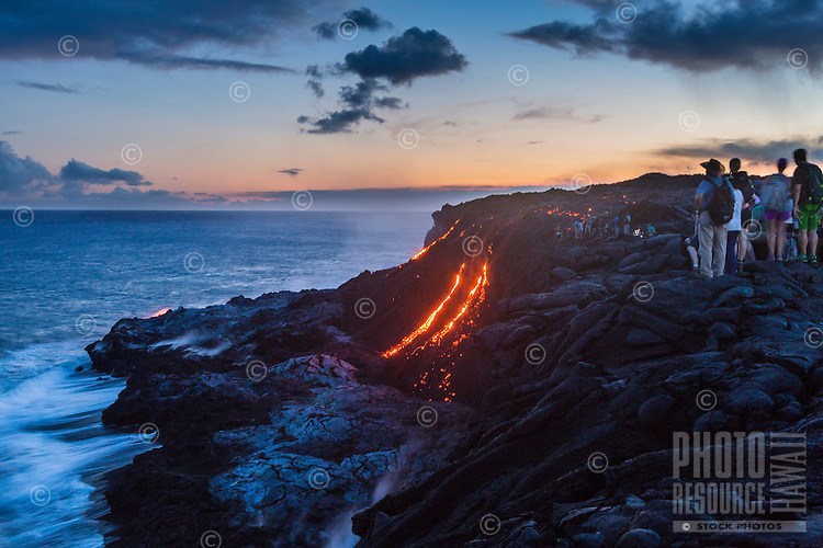 Visitors view the spectacular sight of lava flowing down a cliff and into the ocean at dusk, Hawai'i Volcanoes National Park, Hawai'i Island.