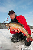Angler holding up a splake caught ice fishing in winter.