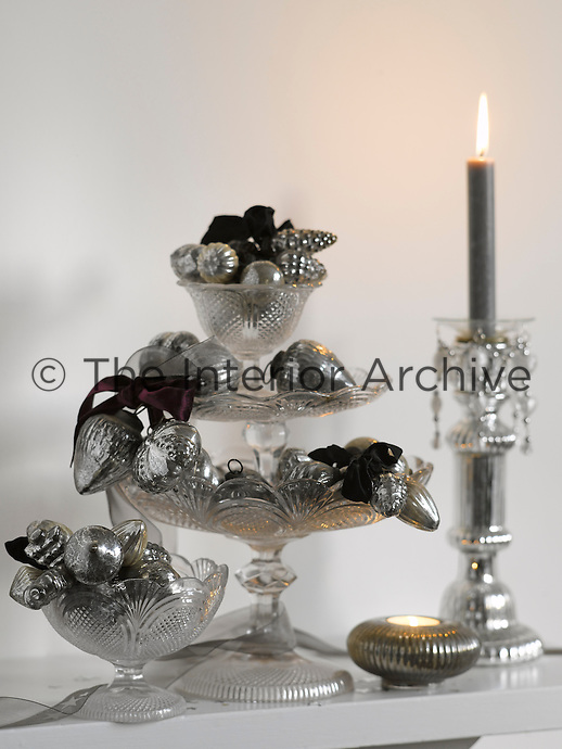 Detail of a three-tiered glass sweet dish filled with silver Christmas decorations