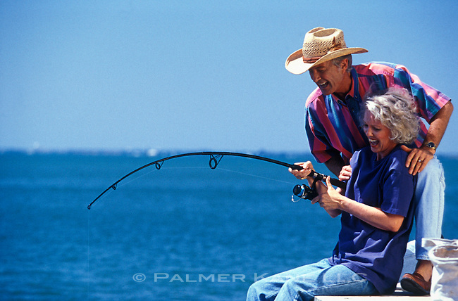 Senior man advising his wife on reeling in the fish she just caught