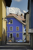 Brightly painted Indigo house and car against  the background of a snow capped mountain.Imst district,Tyrol, Austria.