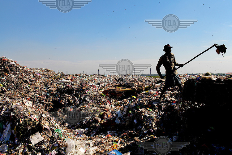 Workers spread out rubbish at a huge dump after it was unloaded from a truck. Dhaka alone generates about 3500 to 4000 metric tons of solid waste each day.