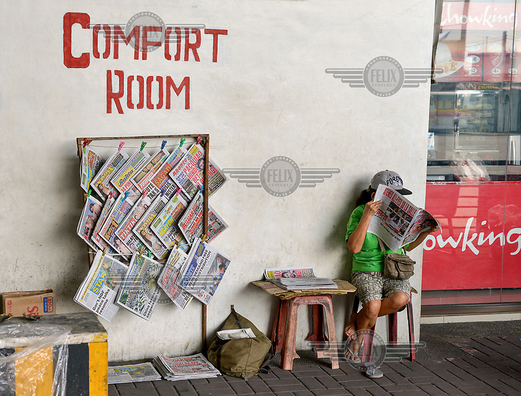 A newspaper vendor reads a paper while waiting for customers at their stall next to a public toilet ('Comfort Room').