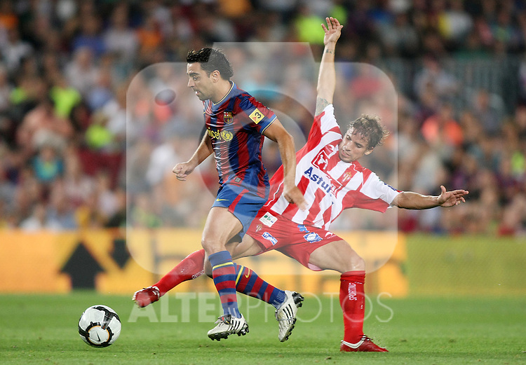 FC Barcelona's Xavi Hernandez (l) and Sporting de Gijon's Alberto Rivera during La Liga match.August 31 2009. (ALTERPHOTOS/Acero).