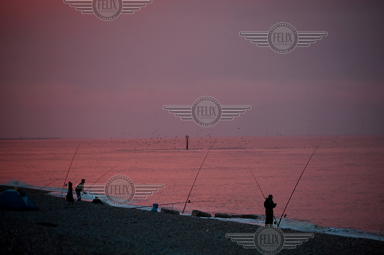 Fishermen try their luck at dusk on the beach in front of Sizewell B Nuclear Power Station, Suffolk....