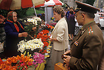 Tallinn Estonia 1980s. A Baltic State country part of the USSR. A Russian soldier waits to buy some flowers from Estonian woman in Viru street flower market 1989