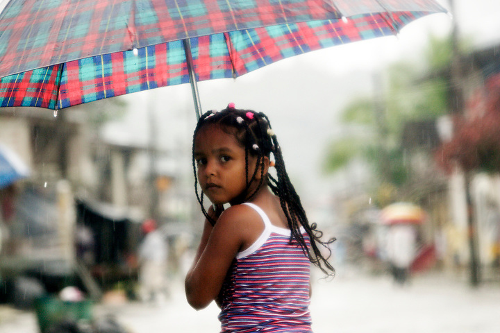 NUQUÍ, EL CHOCO, COLOMBIA -- DECEMBER 12:  A young girl peers out from underneath her umbrella in Nuqui on December 12, 2005. Nuquí is a small town on Colombia's isolated and untamed Pacific coast, an area sandwiched between endless miles of trackless rainforest and the Pacific Ocean. (Photo by Dennis Drenner/Aurora).