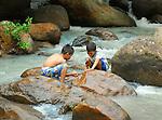 Village near Tegucigalpa, Honduras. Boys playing in stream.