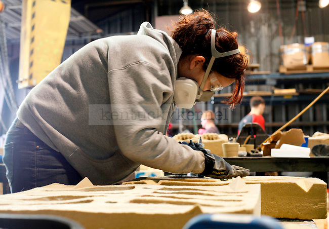 Scuplture graduate student Melissa Van Sandt carves a cast of 99 beer bottles for installation. She was one of the many that participated in the 17th Annual Iron Pour at the Reynolds Building #2 Saturday..Photo by Zach Brake | Staff