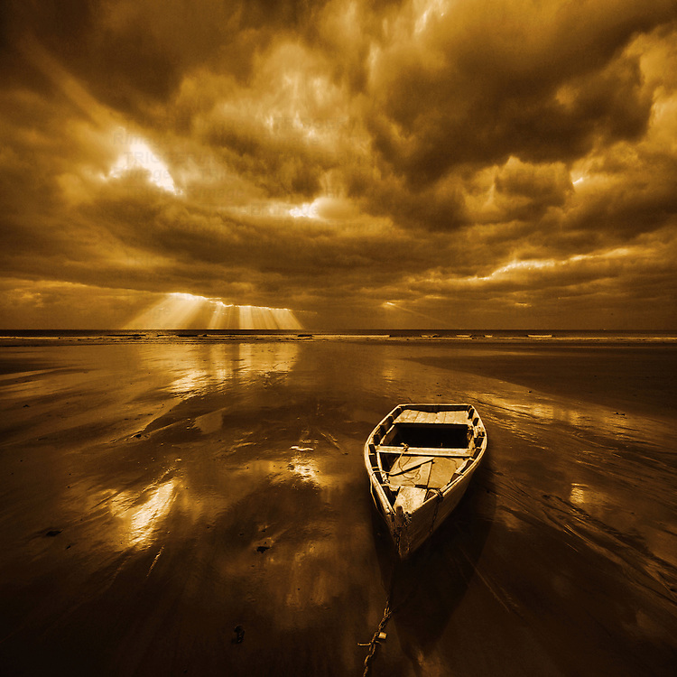 Stormy landscape with dark clouds and dramatic sunlight with wooden rowing boat on shore