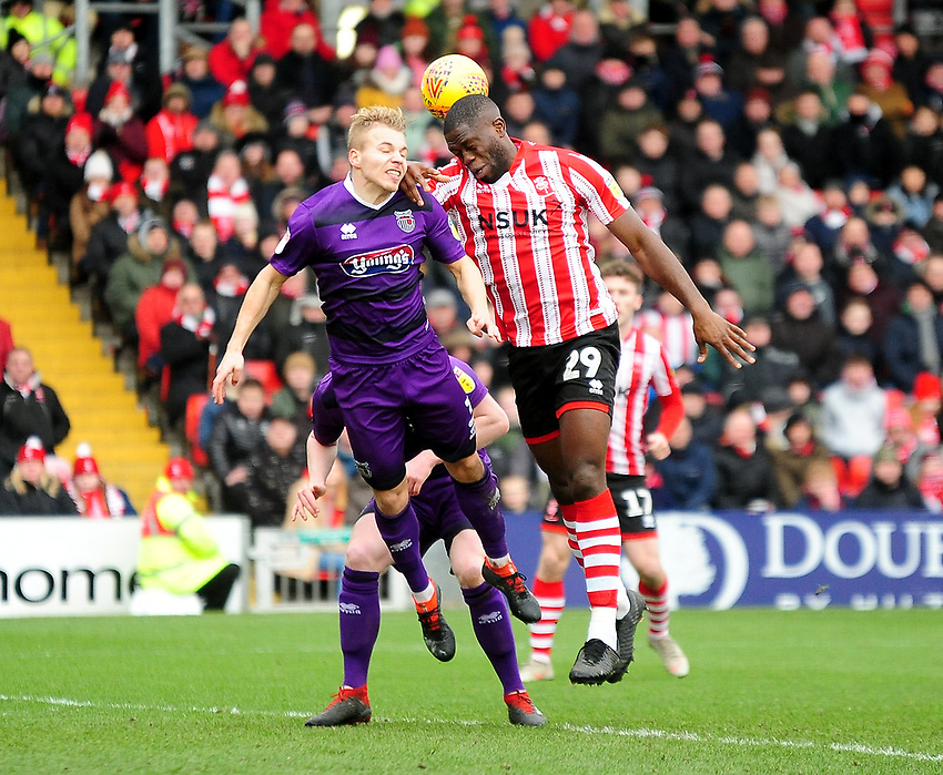 Lincoln City's John Akinde vies for possession with Grimsby Town's Sebastian Ring<br /> <br /> Photographer Andrew Vaughan/CameraSport<br /> <br /> The EFL Sky Bet League Two - Lincoln City v Grimsby Town - Saturday 19 January 2019 - Sincil Bank - Lincoln<br /> <br /> World Copyright © 2019 CameraSport. All rights reserved. 43 Linden Ave. Countesthorpe. Leicester. England. LE8 5PG - Tel: +44 (0) 116 277 4147 - admin@camerasport.com - www.camerasport.com