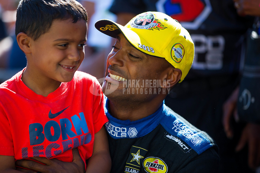 Jun 7, 2015; Englishtown, NJ, USA; NHRA top fuel driver Antron Brown (right) celebrates with son Adler Brown the Summernationals at Old Bridge Township Raceway Park. Mandatory Credit: Mark J. Rebilas-