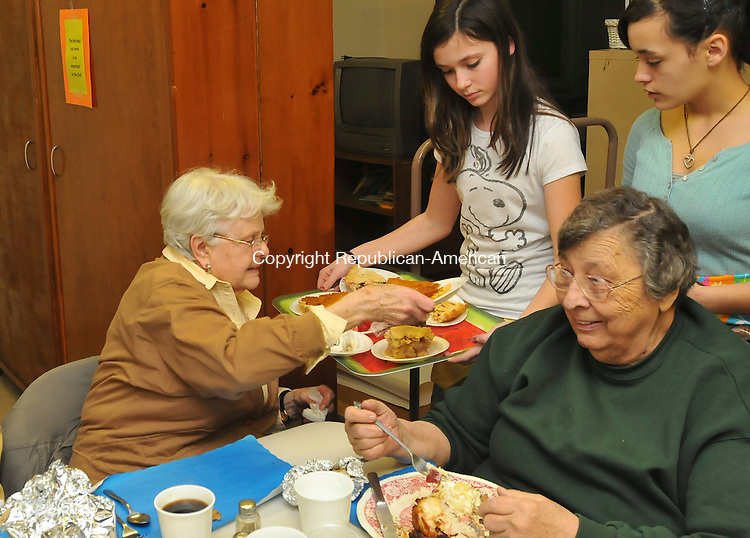 HARWINTON, CT-27 FEBRUARY 2009-022710IP15- Ana Flammia of Burlington and Shyanna Mohagel (far right) of Harwinton serve desserts to Helen Whalen of Harwinton as Mary Stevens of East Hartford eats, at the 48th annual Chicken Barbecue at the Harwinton Congregational Church on Saturday. The church expected 200 eat-in customers and 700 people for the take-out service. The meals included barbecue chicken, baked potato, cole slaw, and home-baked desserts.<br /> Irena Pastorello Republican-American