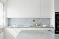 The minimal kitchen features a wall of fitted cupboards with work surfaces and a kitchen island clad in grey marble