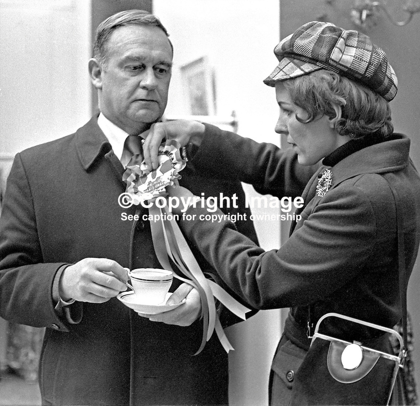 Vanguard Unionist politician, William Craig, at City Hall, Belfast, N Ireland, to hand in his nomination papers for the East Belfast seat in the 28th February 1974 UK General Election. His German-born wife, Doris, pins an election rosette on his lapel. 197402180130b<br />