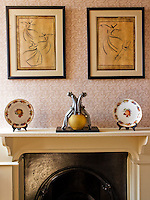 A Pierrot figurine on the mantelpiece between two antique ceramic plates with a pair of sufi inspired drawings above