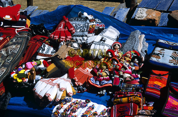 Colourful dolls, gloves and bags on stall in market, La Raya, Puno to Cusco Perurail train journey, Peru