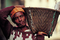 Porter in knitted orange cap and patterned maroon sweater carries straw basket on shoulder. Pashupatinath, Nepal.