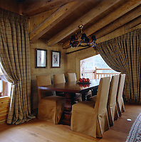 The dining area in a corner of the living room has chairs upholstered in suede and plaid curtains across the windows