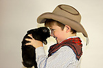 A young cowboy holding a black bunny rabbit