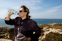 Woman drinking mineral water near the coast of Les Goudes, Marseille, France.