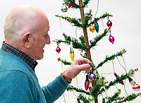 PLEASE BYLINE Hansons Auctioneers Ltd/Athena Pictures<br /> Pictured: Steve Rose decorates his Christmas tree<br /> Re: One of the first mass-produced Christmas trees will be sold at auction after owned by the same family for 80 years.<br /> The parents of Steve Rose, 74, used to decorate the vintage 1937 tree which they bought from Woolworths, every year in their home in Markham, Caerphilly and kept on with the tradition after they died.<br /> But Mr Rose feels it is time to say goodbye and give someone else the chance to create a simple, vintage Christmas.<br /> The tree is offered for sale alongside Mr Rose's lights and baubles and has an estimate of &pound;200-300, but a similar item sold last year without any decorations for &pound;420.<br /> Mr Rose, a retired Biology teacher, the only son of a miner, is parting with his heirlooms because he has no children to leave them to.<br /> &quot;It was our main family tree for years and I remember my mum putting it up every Christmas,&quot; he said.<br /> &quot;Christmas was not an extravagant affair... in the late 1940s you'd get a Christmas sock and inside it was a tangerine, nuts, some loose change and small presents.