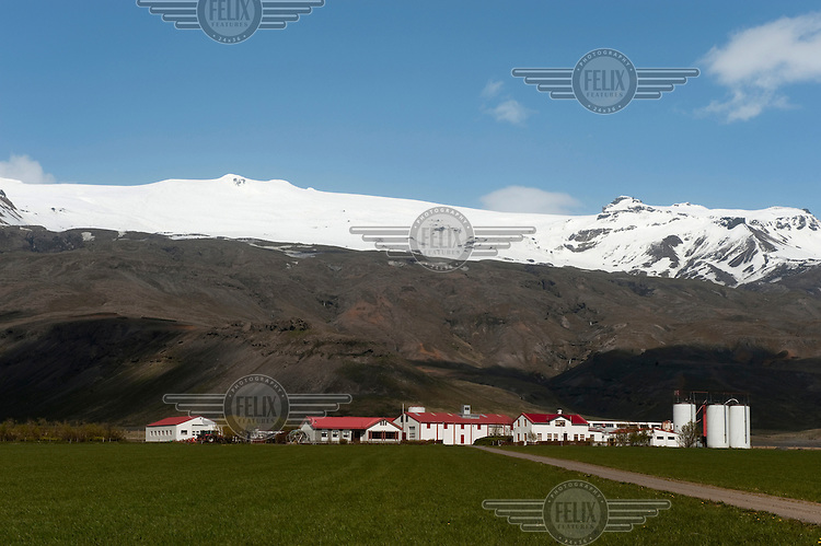 Buildings beneath the Myrdalsjokull ice cap and volcano.