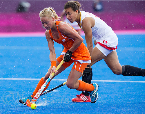 29 JUL 2012 - LONDON, GBR - Maartje Goderie (NED) of Netherlands (left) evades a challenge from Erica Coppey (BEL) of Belgium during their women's London 2012 Olympic Games Preliminary round hockey match at the Riverbank Arena in the Olympic Park in Stratford, London, Great Britain (PHOTO (C) 2012 NIGEL FARROW)