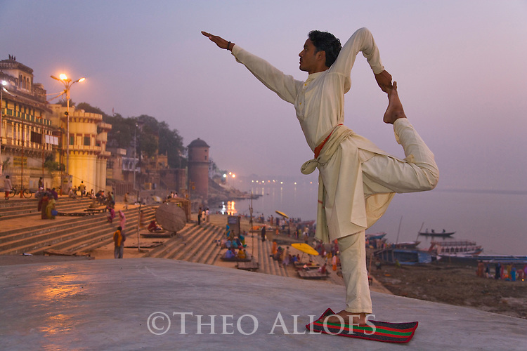 Yoga teacher doing his morning exercise at one of the Ghats (steps) in Varanasi;  Varanasi has been a cultural and religious center in northern India for several thousand years, Varanasi, Uttar Pradesh, India