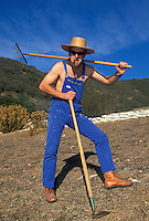 Hans Rey wearing dungarees , straw hat and carrying a rake and hoe<br /> Laguna , California <br /> pic copyright Steve Behr / Stockfile