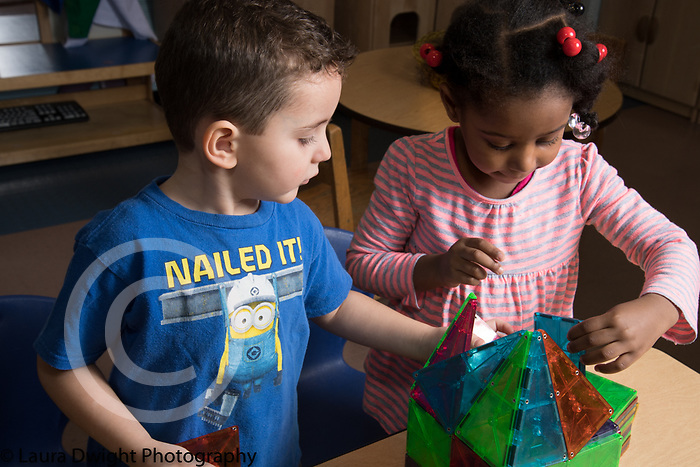 Education Preschool Childcare 2-3 year olds boy and girl working together on magnetic block construction