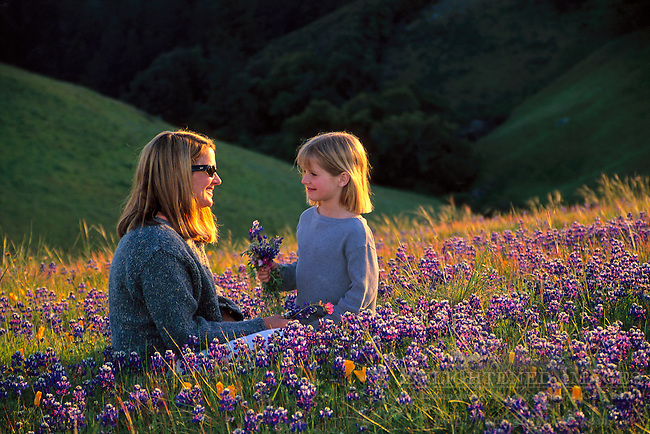 Mother and daughter in field of colorful wildflowers on hillside in spring, Bolinas Ridge, Marin County, California