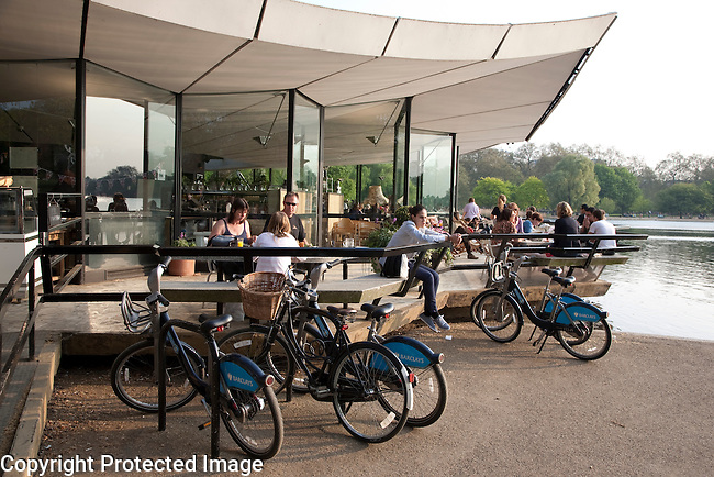 Rented bikes and people taking refreshments in Cafe at the Serpentine in Hyde Park, London, UK