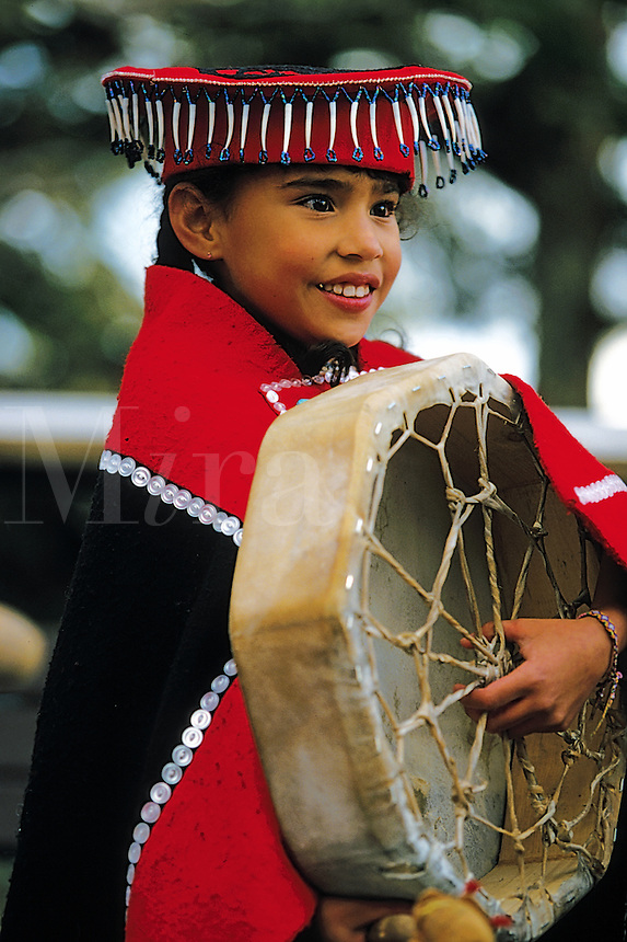 Portrait of a smiling Tlingit Native Alaskan girl as she performs a traditional dance with a drum. Alaska.