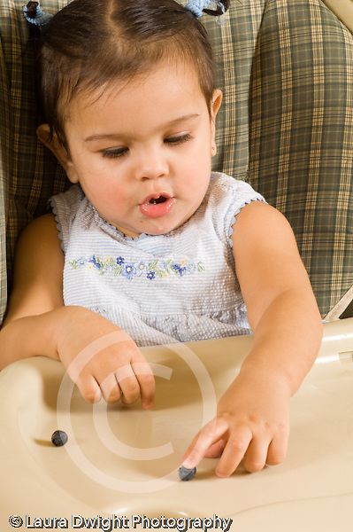 10 month old baby girl in high chair feeding self fuit berries blueberries Hispanic vertical