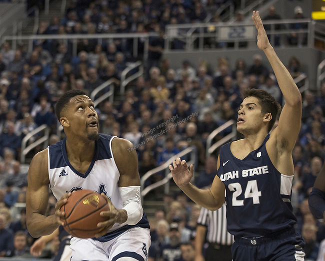 Nevada forward  Tre'Shawn Thurman (0) looks to shoot  against Utah State guard Roche Grootfaam (14) in the first half of an NCAA college basketball game in Reno, Nev., Wednesday, Jan. 2, 2019. (AP Photo/Tom R. Smedes)