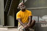 Mature man sitting outdoors, smiling, portrait