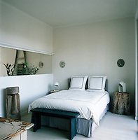 A white bedroom with a painted wood floor and a glass panel in one wall, which allows light into the room. Items of salvaged material contrast with more modern pieces.