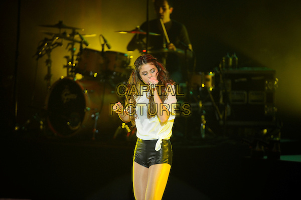 Selena Gomez <br /> performing in concert, Eventim Apollo, Hammersmith, London, England, UK, 7th September 2013.<br /> music live on stage gig half length microphone singing black leather hotpants shorts white top shirt <br /> CAP/MAR<br /> &copy; Martin Harris/Capital Pictures