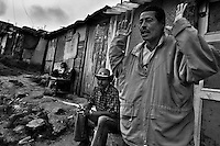 A displaced man from Caquetá department talks in front of his house in the shanty town of Ciudad Bolívar, Bogota, Colombia, 30 May 2010. With nearly fifty years of armed conflict, Colombia has the highest number of civil war refugees in the world. During the last ten years of the civil war more than 3 million people have been forced to abandon their lands and to leave their homes due to the violence. Internally displaced people (IDPs) come from remote rural areas, where most of the clashes between leftist guerrillas FARC-ELN, right-wing paramilitary groups and government forces takes place. Displaced persons flee in a hurry, carrying just personal belongings, and thus they inevitably end up in large slums of the big cities, with no hope for the future.