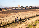 Family walking by the village and castle looking across fields, Orford, Suffolk, England