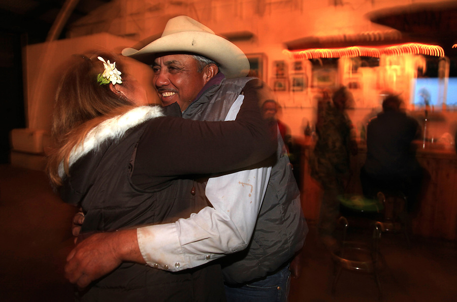 "Godfrey Kainoa, one of the few known descendents of the original Mexican ""vaqueros"" who taught the Hawaiians their cowboys skills, dances with his girlfriend, Johnelle ""Amoo"" Ching in the Kahua Ranch barn in North Kohala, Hawaii--which sports a bar--after a long day of branding.  Kainoa is employed as a cowboy by Kahua Ranch and through the Hawaiian Homelands Commission Act, leases land on which he raises his own cattle."