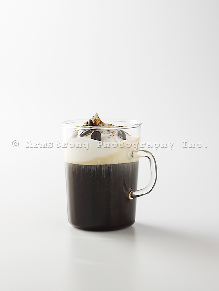 Hot coffee drink in a glass mug with whipped cream, nutmeg, and espresso beans. On a white background.